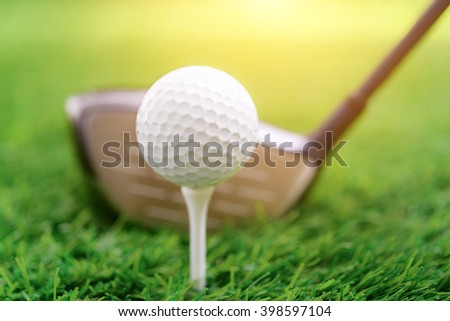 Golf club and ball on green grass, soft focus