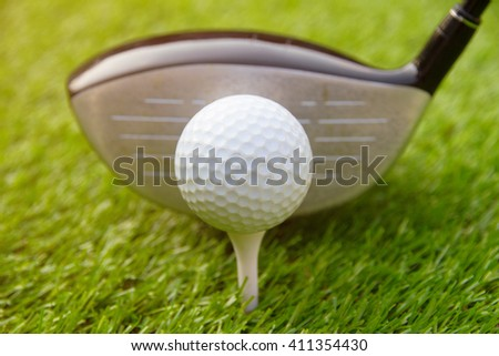 Golf club and golf ball on grass green in summer