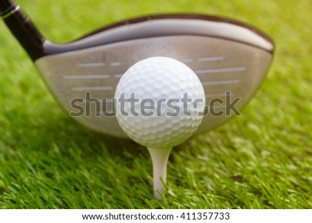 Golf club and golf ball on grass green with sunlight