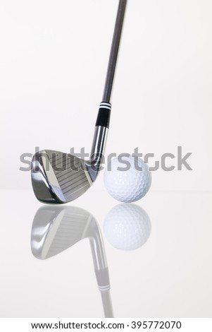 Golf club and golf ball on the glass table