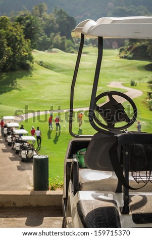 Golf club cars at golf field with golfers are on started point