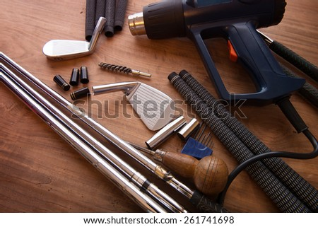 Golf club making or club assembly. Iron club heads and steel shafts with assembly tools on work desk or work bench. Intentionally shot with low key shadows. - stock photo