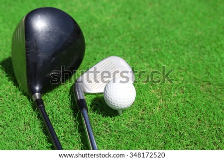 Golf clubs and ball on a green grass