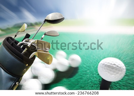 Golf clubs drivers and golf ball over green field background  - stock photo
