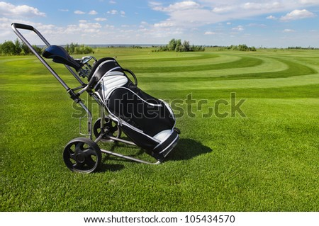 Golf clubs in golfbag and golf balls green grass background - stock photo