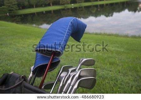 Golf Clubs near a water trap/Playing the Links/Sports equipment ready for use on a fairway