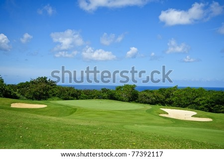 Golf course against deep blue sky with clouds and sand pools under white puffy clouds and the caribbean sun in tropical barbados in the western corner of the island