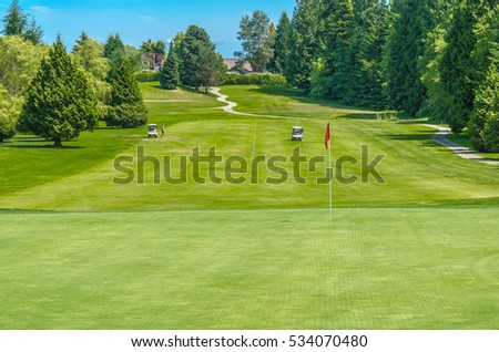 Golf course and a red flag in a sunny day. Canada, Vancouver.