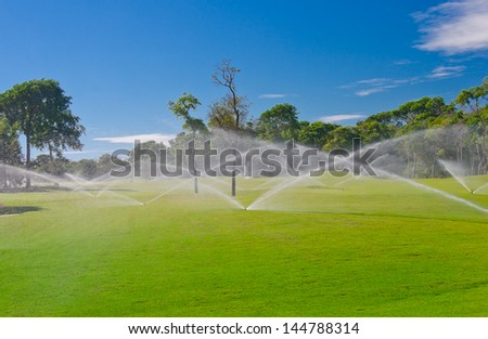 Golf course gets irrigated. Golf field, course sprinkling.  Mexican resort. Bahia Principe, Riviera Maya. - stock photo