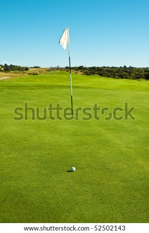 Golf course green with flag and ball in late afternoon sun