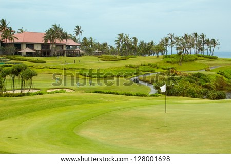 Golf course in luxury resort. Golf green field on the background of the sea and beautiful palm tree over blue sky with white clouds view