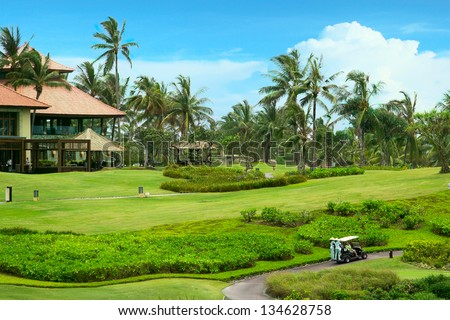 Golf course in luxury resort. Golf green field on the background of the sea and beautiful palm tree over blue sky with white clouds view - stock photo