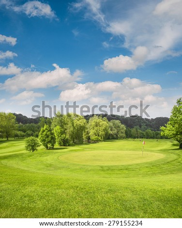 Golf course landscape. Spring field with green grass, trees and cloudy blue sky - stock photo