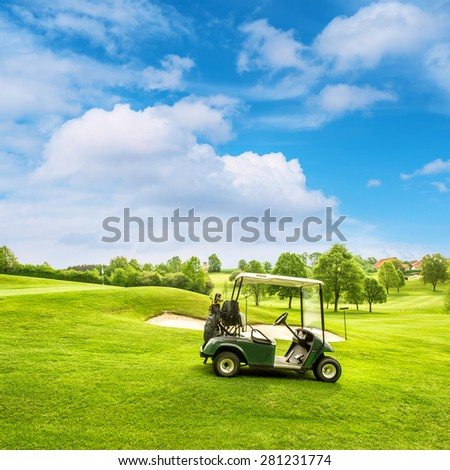 Golf course lanscape with a cart over blue sky background - stock photo