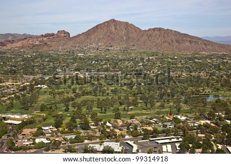 Golf Course, palm trees and upscale housing at the base of Camelback Mountain in Phoenix, Arizona - stock photo
