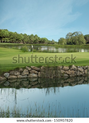 Golf course, the flag and the lake - stock photo