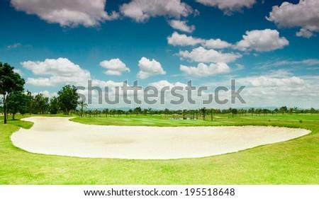Golf course under vibrant cloudy sky - stock photo
