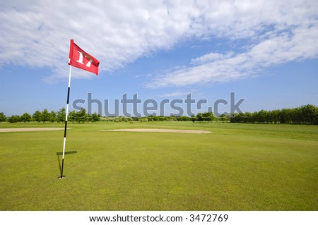 Golf course with blue and cloudy sky.