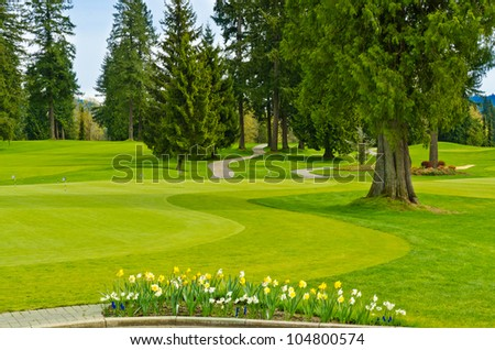 Golf course with gorgeous green and flowers. - stock photo