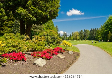 Golf course with gorgeous green and flowers - stock photo