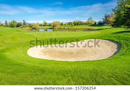 Golf course with gorgeous green and sand bunker - stock photo