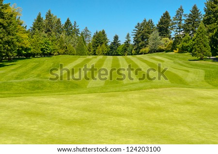 Golf course with gorgeous green over blue sky - stock photo