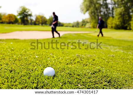 golf course with players, note shallow depth of field