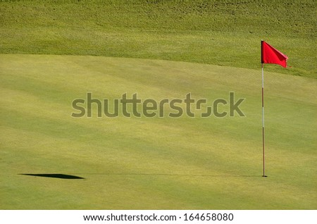 Golf course with red flag in the hole - stock photo