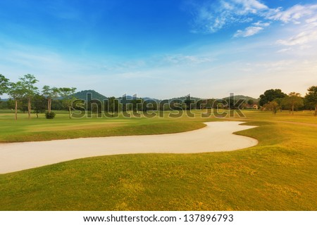 golf course with sand trap near fairway.