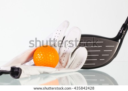 Golf driver and white glove on a glass desk - stock photo
