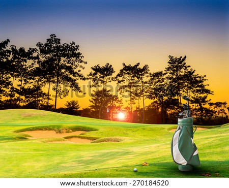 golf equipment on green and hole as background. - stock photo