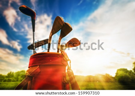 Golf equipment. Professional golf clubs in a leather baggage at sunset - stock photo