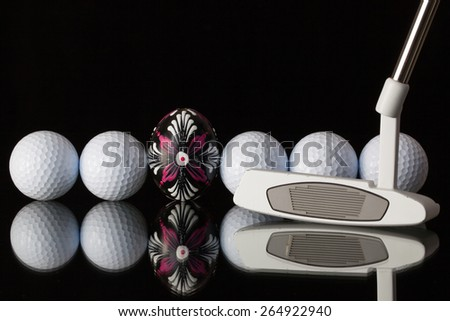 Golf equipments and egg on a black glass desk - stock photo