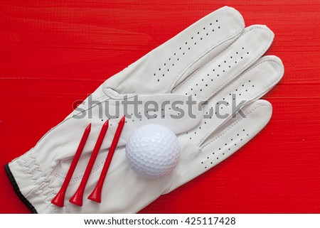 Golf equipments on the wooden red table - stock photo