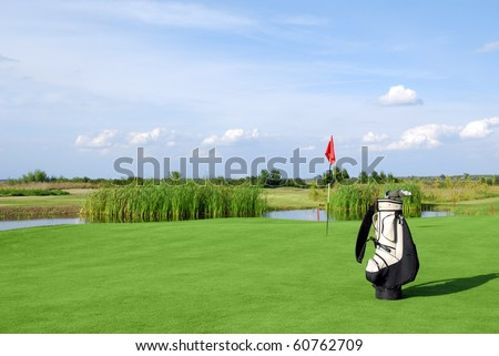 golf field with flag and golf bag - stock photo