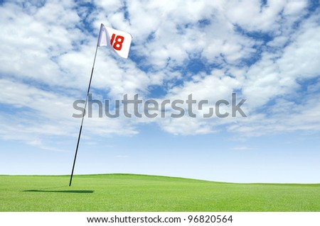 Golf flag at hole 18 on the putting green - stock photo