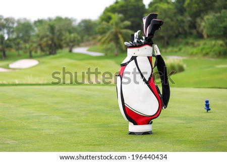 Golf game. Golf clubs in bag against the golf course - stock photo