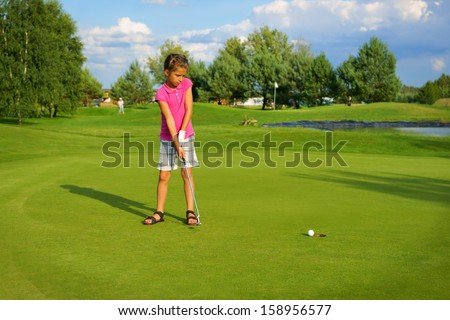 Golf, girl golfer driving ball into the hole