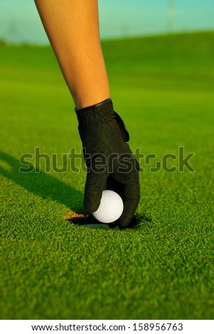Golf, golfer hand retrieving the ball in hole