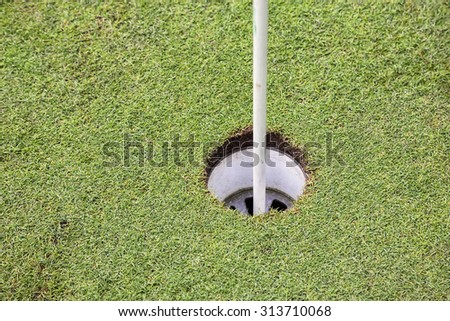 golf hole and flag pole on a field with the green grass. Made with shallow depth of field. - stock photo