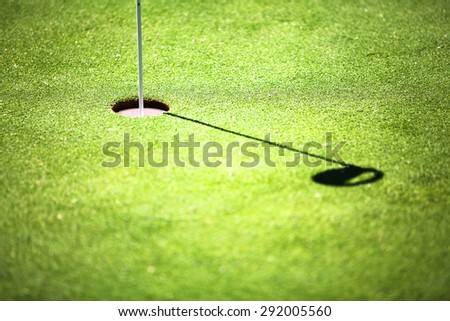 Golf hole in putting green. The putting green is a mini golf course to practice the putter golf shot. - stock photo