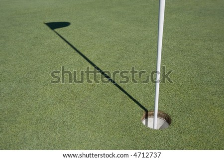 Golf hole with shadow of flag - stock photo
