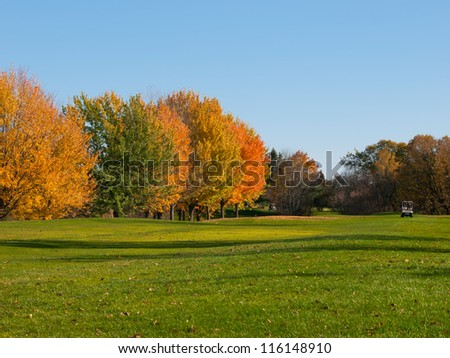 Golf in fall with cart on the fairway - stock photo