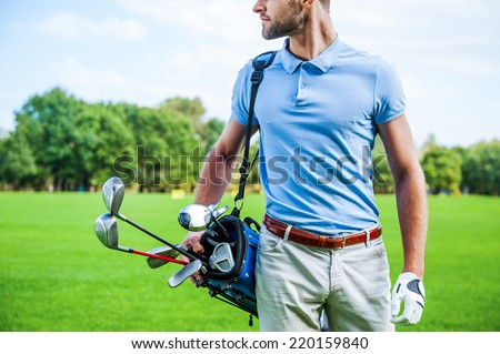 Golf is a style of living. Cropped image of male golfer carrying golf bag with drivers while walking by green grass - stock photo