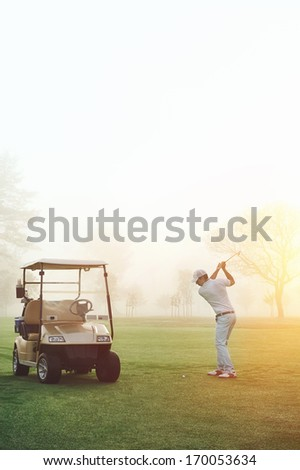 golf man at sunrise playing shot from fairway with cart nearby - stock photo