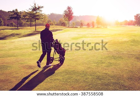 Golf man player walking on fairway with trolley and clubs during sunset in golf curse. - stock photo