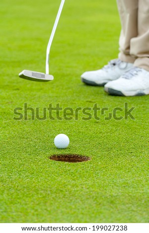 Golf man putting on green - stock photo