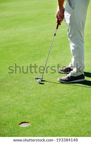 Golf man putting on green and aiming to sink golf putt shot on course