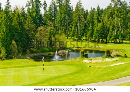 Golf place with gorgeous green and pond. - stock photo