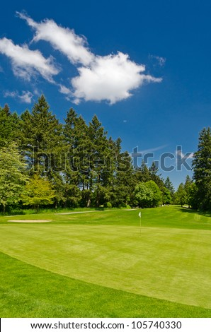 Golf place with gorgeous green and sand bunker.